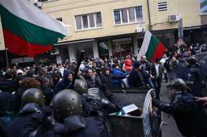 People challenge the riot police as they block traffic during a protest against high electricity bills in Sofia