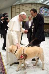 Pope Francis I greets a man with a guide dog as he conducts a general audience in the Paul VI hall for members of the media at the Vatican
