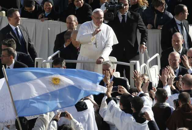 Pope Francis approaches priests with an Argentine flag as he arrives in Saint Peter's Square for his inaugural mass at the Vatican