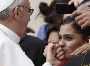 Woman kisses Pope Francis' hand as he greets guests during general audience in St. Peter's Square at Vatican