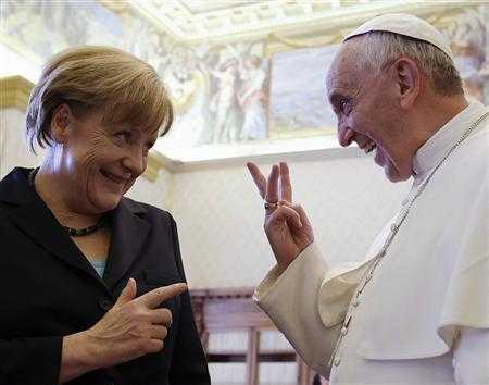 Pope Francis gestures as he talks to German Chancellor Angela Merkel during a private audience at the Vatican
