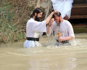 An Orthodox Christian priest baptises a man on the eastern bank of the Jordan River, Jordan, for the feast of Epiphany