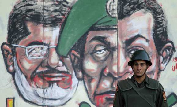 A soldier stands in front of a mural drawn on the wall of the presidential palace in Cairo