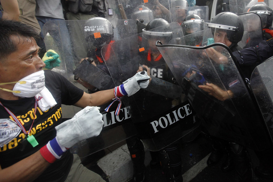 An anti-government protester fights with the police at the barricade near the Government house in Bangkok