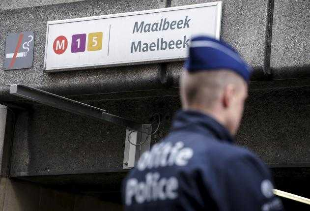 A Belgian police officer stands guard outside the metro station of Maalbeek in Brussels