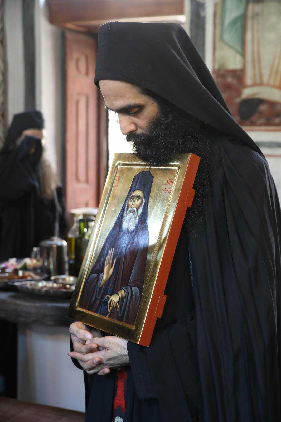 The presiding priest in the refectory with the icon of St Paisios.