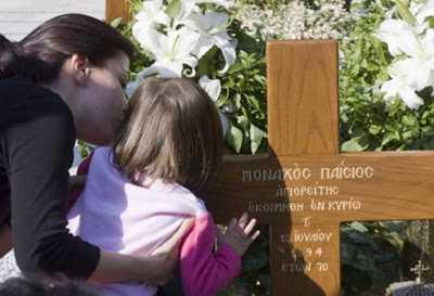 copil saruta crucea Cuv. Paisie