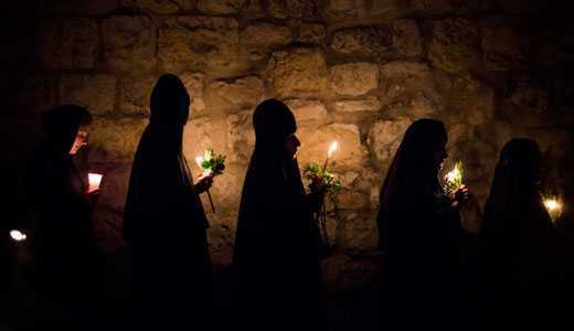 Christian Orthodox nuns hold candles and flowers as they walk along the Via Dolorosa in the old city of Jerusalem