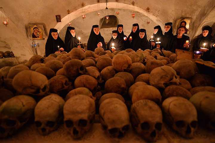 Romanian Orthodox holds candles inside to the ossuary of Pasarea monastery