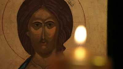 stock-footage-lighting-candle-in-front-of-jesus-christ-orthodox-icon-praying-moment