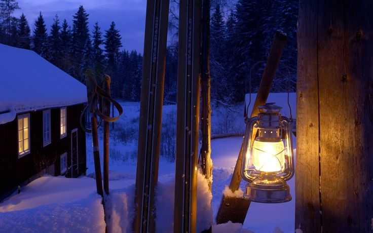 Close-up of lit lantern at gatepost, Sweden
